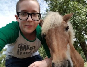 Image of Courtney Kirkham in a MapThis! t-shirt standing next to a miniature horse.