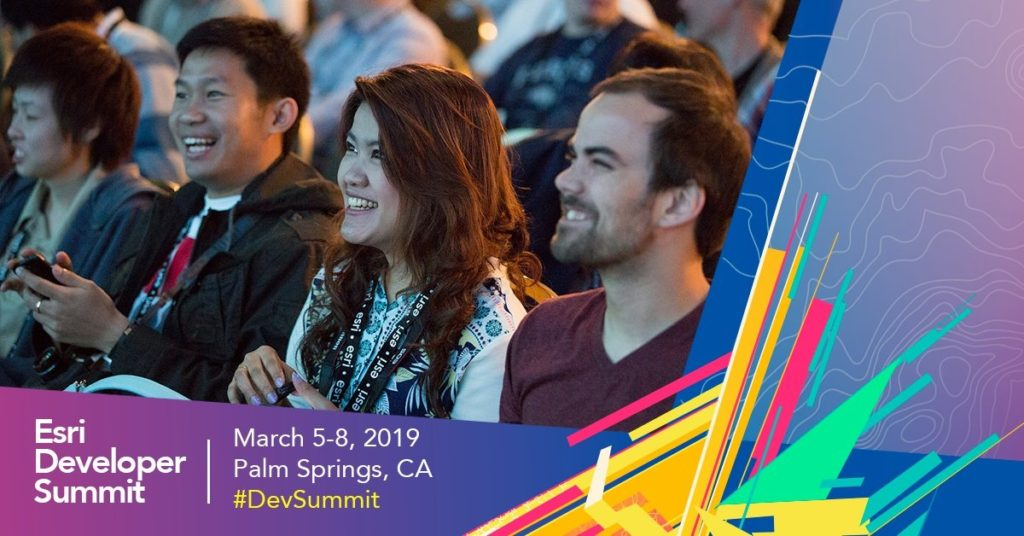 People sitting in a crowd, focus on a woman and two men. They are looking at a screen or presentation to the left of the image that is illuminating their faces. There is a banner along the bottom of the image with the text, Esri Developer Summit, March 5-8, 2019, Palm Spring, CA, #DevSummit.