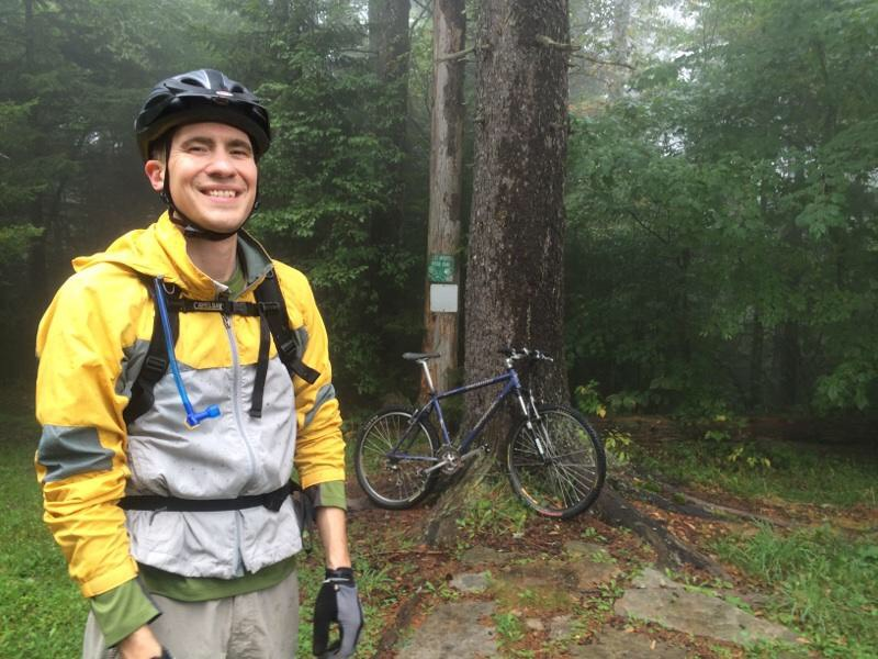Tim standing on a trail in a forested area wearing a helmet and backpack. Trees in background with a bike leaning against a tree.