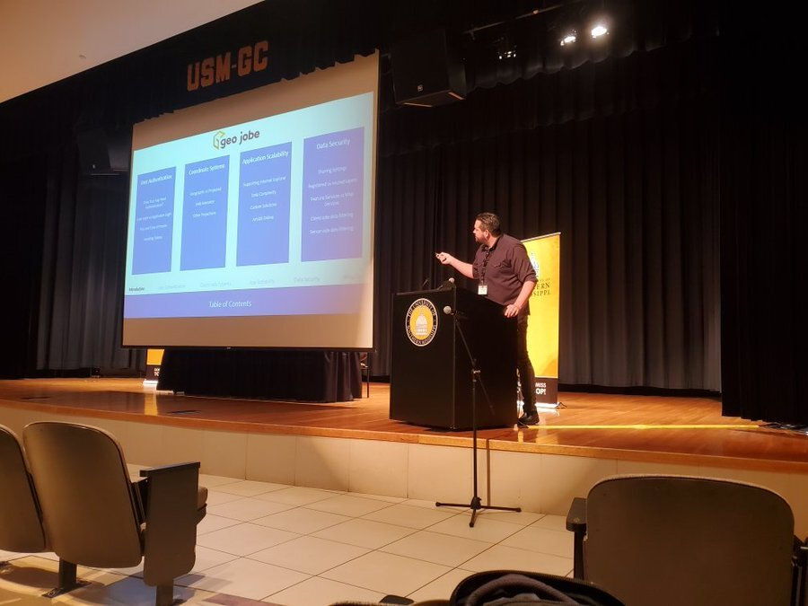 Eric Goforth stands at a podium on a stage. He is leaning forward and using a laser pointer to direct the audience's attention to a specific section of on a presentation that is being projected on a large banner next to him. The presentation currently shows four columns outlining the content of the presentation.