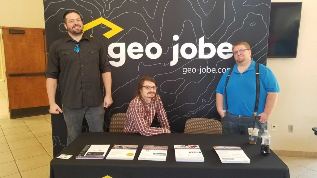 Eric Goforth, Brice Jones, and Danny Menikheim are standing in front of the GEO Jobe booth that the Mississippi Geospatial Conference. Flyers for various products and services are laid out in front of them.